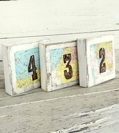 Charming for the world traveling couple or at a destination wedding, these wooden table numbers are a rustic roadmap for your guests. Each table sign features distressed steel numbers held on with tacks and portions of a found map on a whitewashed wooden block. The table numbers are all double sided, so everyone can follow the map from any direction.