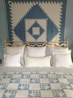 Displaying a lovely quilt as a wall hanging, with another blue and white on the bed. Very cottage home sweet!  Vintageblessings