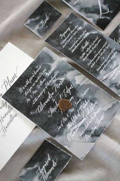 Una invitación fantástica con acuarelas en tonos oscuros, caligrafía y sello en dorado.
