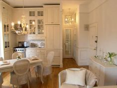 tiny ny studio's amazing transformation from bleak to chic | here's the dining room and kitchen | tall ceiling, wood floor, whites, chandies...