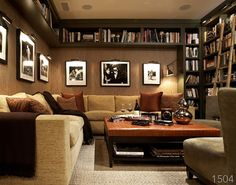 This cozy den has tons of seating, rich textures and fabrics that have an overall masculine feel.  This room showcases this homeowner's black and white artwork collection and  extensive library. And it provides ample space to stretch out.