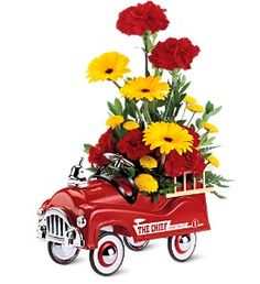 """Make him feel like a kid again with bright flowers in a blazing red metal fire engine, complete with rubber-tired wheels that roll.    Alstroemeria, Chrysanthemums, Solidaster, and Carnations delivered in a keepsake gift.    Truck measures 6 3/8"""" (H) x 4 3/4"""" (W). Arrangement approximately 9"""" (W) x 15"""" (H)"""