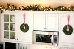 kitchen christmas by a thoughtful place - love the lights and greenery above the kitchen cabinets & wreaths hanging from pretty ribbon on the cabinets