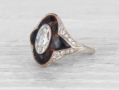 Art Deco Tiffany & Co ring made in platinum centered with an EGL certified approximately .90 carat E-F color VS1 clarity oval cut diamond surrounded by 8 fancy cut onyx. Accented by 20 single cut diam