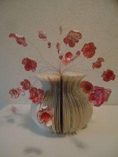 Mal gemaakt van karton, boek uitgesneden langs de mal.Bloemen van restjes bladzijden en gekleurd met waskrijt.Omgekruld met een schaar en op een dun rood staaldraadje gezet.