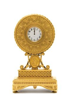 E.F. Caldwell Gilt-Bronze Mantel Clock  In the Neoclassical style, the white enameled circular dial with black Arabic numerals, surrounded by a conforming case decorated with anthemion motifs, on scrolling supports centering an oval portrait medallion depicting a classical female in bas relief, continuing to a stepped rectangular base ending in bun feet.