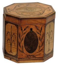 A George III Satinwood and Marquetry Tea Caddy, late 18th Century. Of octagonal form, the hinged cover with monogram, the sides with oval reserves 5½ in. (14 cm.) high- Christies
