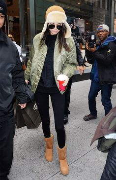 Kendall Jenner wears a black sweater, olive green bomber, leggings, Ugg boots, aviator sunglasses, and a shearling trapper hat