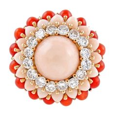 Diamond Pink & Red Coral Yellow Gold Dome Ring, 1950's. Designed as a play on a classic cluster style, with a single cabochon cut angel skin coral bursting from the center, framed with graduated halos of diamonds, then more angel skin coral and natural red coral. In total, sixteen diamonds weigh approximately 1.50 carats.