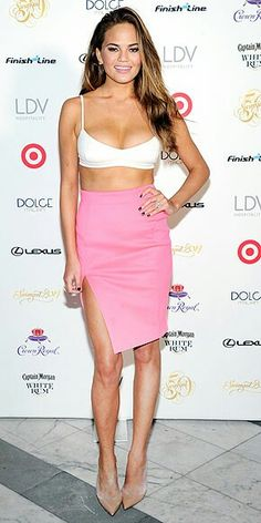 03a51195ae6 Sports Illustrated Swimsuit Model Chrissy Teigen white bra top and pink  thigh-high slit skirt