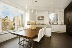 This NYC kitchen has large tile flooring, white cabinetry, a marble style wall covering, delicate pendant lighting, a large wooden community table and a beautiful view of the city.