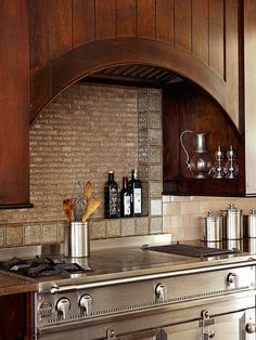 Range Hood Ideas : A high arch made out of wooden panels keep in line with this kitchen's country English aesthetic. The dark wood contrasts stainless-steel appliances and a neutral backsplash. Kitchen Hood Design, Kitchen Vent Hood, Kitchen Exhaust, Kitchen Stove, New Kitchen Cabinets, Kitchen Designs, Stove Vent Hood, Stove Hoods, Hickory Kitchen
