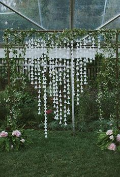 whimsical DIY ceremony altar wrapped in wild vines with hanging cone garlands