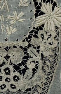 Handmade mixed lace boudoir throw, c.1900. The center medallion of handmade bobbin lace portrays a lady and gentleman in a garden. The panel is surrounded with a larger medallion of fine batiste, hand-embroidered with padded satin-stitch flowers. As the eye moves outward, it encounters an harmonious collection of hand-assembled tape lace, Brussels bobbin lace, and Cluny lace as well as fine embroidery.