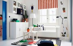 A bright living room with a two-seat sofa, a square-shaped side table and storage, all in white. Combined with a striped curtain in orange/white and a rug with a fun match-pattern.