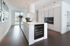 Erg modern, maar wel heel gaaf deze witte design keuken. Opvallend detail; de wijnklimaatkast ingebouwd op de kopse kant van het werkeiland...Keukendealer: tielemankeukens.nl