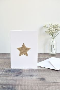 """A lovely handmade gold star card.  Made from gold glitter fabric the star is stitched directley onto the card using freehand machine embroidery. This simple but elegant card can used for any occasion such as a birthday card or """"you're a star"""" thank you card.  #starcard #goldstar #handmadecards #embroideredcard #embroideredcards #stitchedcard #stitchedcards #sewncard #fabriccards #specialcards  #uniquecard  #uniquecards  #custommadecards  #freehandmachinembroidery #freemotionembroidery Glitter Stars, Gold Stars, Gold Glitter, Freehand Machine Embroidery, Free Motion Embroidery, Fabric Stars, Glitter Fabric, Unique Cards, Card Envelopes"""
