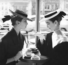 Two ladies in hats and gloves having tea.
