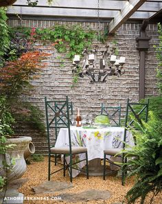A concrete table paired with four iron chairs, which were a find made by Robinson's designer Jayson Cain of Jayson Cain Interiors, makes for an informal yet sophisticated setting. | A Gracious Planting | At Home in Arkansas | July 2016 | outdoor living