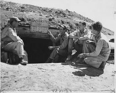 """""""Dash-Rite Inn. Through these portals pass the fastest men on earth."""" They do it too - Marine pilots of the little """"Grasshopper"""" observation planes on Yontan airfield Okinawa have a sign over the entrance to their bomb shelter which tells how rapidly they take cover when it is necessary (L to R) 2nd Lieutenant Donald H. Rusling Captain Donald R. Garrett 2nd Lieutenant Lester E. Bartils and 2nd Lieutenant Glenn R. Hunter."""
