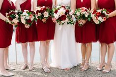 {{Wedding party in red bridesmaid dresses holding bouquets of dahlias, garden roses, berries, vines in red, coral, peach, blush at a late summer wedding at Galleria Marchetti in Chicago.}} Photography by Laura Fisher Photography http://www.laura-fisher-photography.com/ || Flowers by Pollen, pollenfloraldesign.com