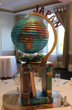 Geography themed Bar Mitzvah Centerpiece. Hand painted globe lantern  on a base of hand made, hand painted antique books! Very unique and very stunning. www.give-em-props-studio.com