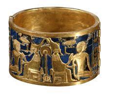Brazalete de  Queen Ahhotep, / Ahmosis  Está formado por dos planchas de oro y lapislázuli, en forma de cilindro, unidas con bisagras. En él vemos a Ahmosis de rodillas recibiendo la realeza de Geb, el dios de la tierra. Pertenece al tesoro funerario de la reina Ahhotep, madre del faraón Ahmosis.