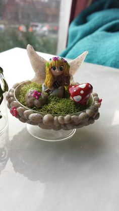 This is a wonderfully beautiful piece that stands just under 3 inches tall. It is made from polymer clay, a glass display dome and some moss. Also this precious fairy is holding the key to her home. All items are hand sculpted and carefully placed with tons of tiny detail. There are stones wrapped around the bottom of her home joined by some cute pink flowers. Inside you see a fairy sitting on a tree stump, a rock with some moss and a tiny purple butterfly. As well as a toadstool next to the…