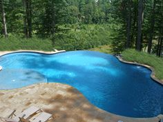 This swimming pool design has a disappearing edge, decking of travertine pavers, a tanning shelf and a beautiful waterfall...all making the project amazing. The rear yard was located on a cliff so taking advantage of the view was a priority.