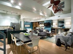 In this urban loft, a color palette of gray, black and white is paired with shimmery steel and rich wood accents for a cool, contemporary vibe. Modern furnishings, smart track lightings and a dramatic ceiling fan combine for a stylish and functional living space.