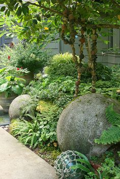 Concrete balls nestled in shade garden... in the PNW and other wet areas, these will soon turn into moss balls!