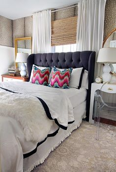 head board with white bedding and pops of c olor and pattern