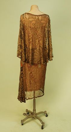 Back View BEADED GOLD METALLIC LACE DRESS with FAN MOTIF, c. 1920. Sleeveless with attached capelet, the lace in a ginko leaf pattern, a band of bugle bead fans in rose, cobalt, gold and silver circles the draped waist and adorns a flounce on left side, seams and edges trimmed with a band of gold beading, sand lining with lame straps.