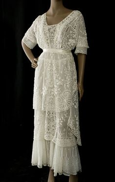 A hand-embroidered tulle tea dress, c.1912. The three skirt layers in the ingenious asymmetrical design lend a dignified charm to the happy bride. The two outer layers are hand embroidered with a floral pattern of raised padded satin stitch with eyelet accents.