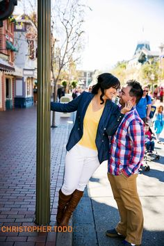couple kisses during engagement session at disneyland photo