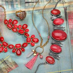 Red, pink, rose gold, gold, and champaign crystals atop statement necklaces, earrings, and rings.