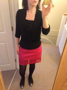Hot pink skirt with square cut out detail, black top and short cardigan, black ballet flats, pearls.