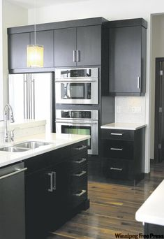 Dark expresso cabinets topped with white quartz countertops create drama in the kitchen.