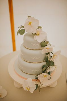 Three tier wedding cake decorated with fresh orchids. Image by A Little Picture