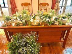 高砂装花はホワイト・グリーン・イエローをメインに、挿し色としてパープルを用いています。ガラス瓶や切り株、モスを並べてナチュラルかつおしゃれな仕上がりです!ご新婦さまもお気に入りだそうですよ◎ 足元にもお花があるのが素敵です♡