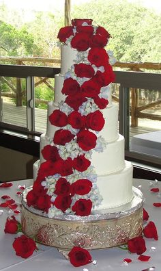 Beautiful white wedding cake with purple and red flowers trailing down the cake.