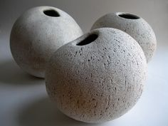 Yumiko Kuga.  Must be pinch pot, but I wonder what sort of glaze???  Very earthy!  If you textured your pinch pots and smoke fired them after bisque firing, you could probably get something similar and even more interesting.  I'm off to pinch some clay!!