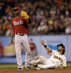 San Francisco Giants' Angel Pagan, right, gestures after being tagged out by Arizona Diamondbacks' Didi Gregorius on an attempted steal of second base in the third inning of a baseball game Wednesday, Sept. 10, 2014, in San Francisco. (AP Photo/Ben Margot)