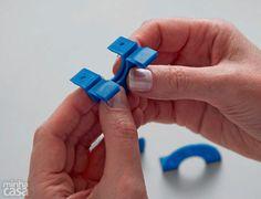 No método tradicional de fazer pompons, são usados círculos de papelão com um furo no meio, porém eles resistem a poucas bolinhas, já que rasgam facilmente. Aqui, preferimos um acessório formado de quatro arcos plásticos, encaixados em pares, que rende pompons de 4 cm.