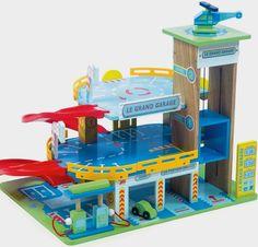 Un grand garage en bois peint de trois étages de la marque Le Toy Van avec 2 rampes d'accès en spirale, un ascenseur à véhicule, un héliport. L'ensemble comprend 1 petite voiture, un hélicoptère et une station service à essence. A partir de 3 ans+