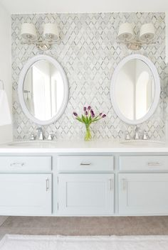 Neutral Master bathroom idea with white Caesarstone countertops and a really fun backsplash wall. His and her sinks with oval framed mirrors and 2-light wall sconces. Floating dual vanity with shaker cabinets.