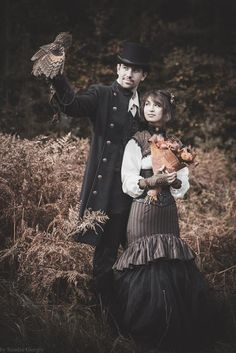 Sophisticated Steampunk Couple with falcon! (woman: striped trumpet skirt, bolero jacket, blouse, choker; man: coat, waistcoat, top hat)  - For costume tutorials, clothing guide, fashion inspiration photo gallery, calendar of Steampunk events, & more, visit SteampunkFashionGuide.com