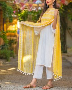 Straight kurta in pure cotton slub fabric detailed with half chinese collar, front pearl buttons, bell sleeves enhanced with crochet lace details. The entire set is teamed with narrow cotton pants and printed chiffon pompom dupatta. Pakistani Fashion Casual, Pakistani Dresses Casual, Pakistani Dress Design, Pakistani Kurta Designs, Indian Wedding Outfits, Indian Outfits, Indian Dresses, Indian Attire, Indian Wear