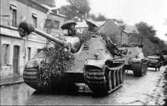 Two German Jagdpanther's move through a village during rainfall so they won't encounter any Allied air support. As you can see, two crew members of the first tank have their umbrellas out. September, 1944.  #ww2 #wwii #rain #jagdpanther