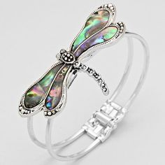 Silver tone dragonfly bracelet with abalone shell and hinged closure.